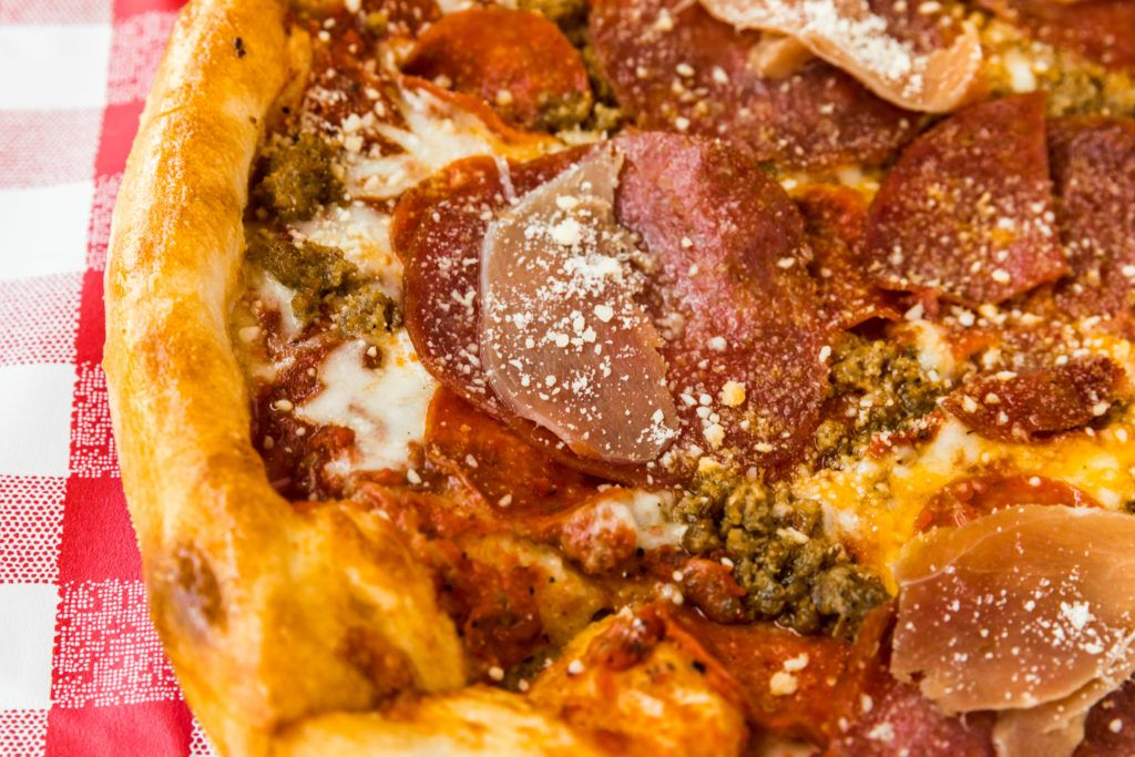 Close up shot of the Meat Packing District Pizza with pepperoni, ham, and Italian sausage.